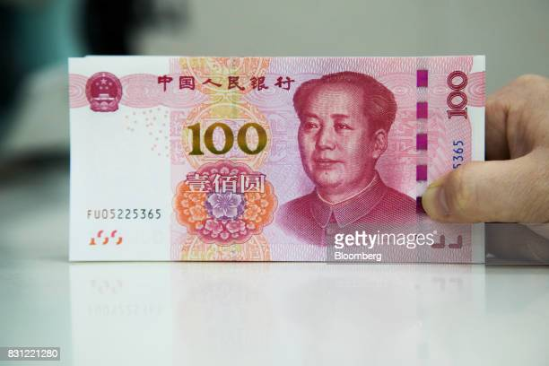 An employee holds genuine Chinese onehundred yuan banknotes at the Counterfeit Notes Response Center of KEB Hana Bank in Seoul South Korea on Monday...