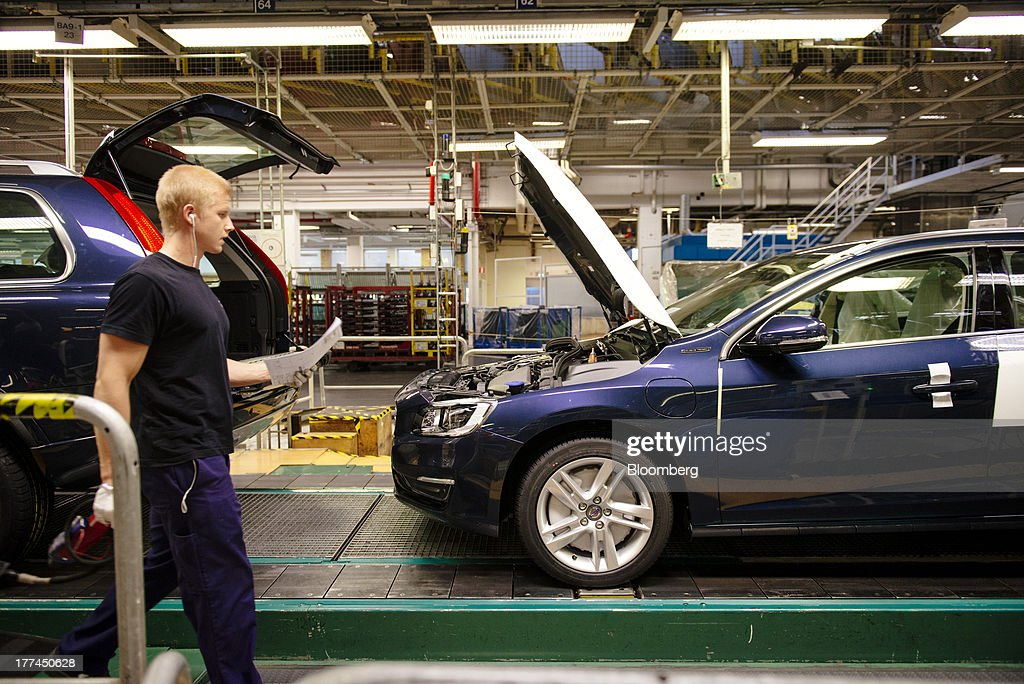 An employee holds paper notes as he walks past vehicles on the production line at the Volvo Cars plant in Torslanda, Sweden, on Thursday, Aug. 22, 2013. Volvo Cars Chief Executive Officer Hakan Samuelsson will settle a German investigation into corruption allegations linked to his tenure as MAN SE's CEO by paying 500,000 euros ($668,000) to charity. Photographer: Kristian Helgesen/Bloomberg via Getty Images
