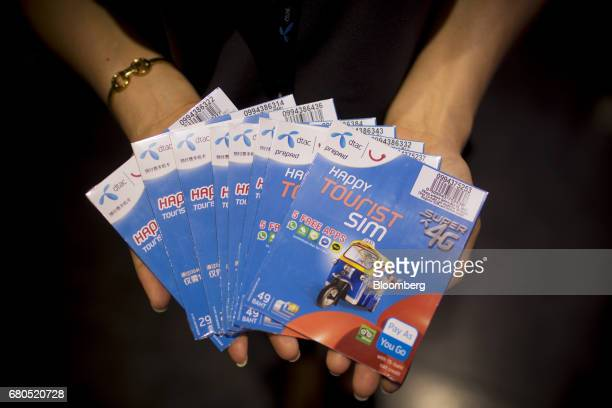 An employee holds prepaid tourist SIM cards for an arranged photograph inside a Total Access Communication Pcl store in Bangkok Thailand on Wednesday...