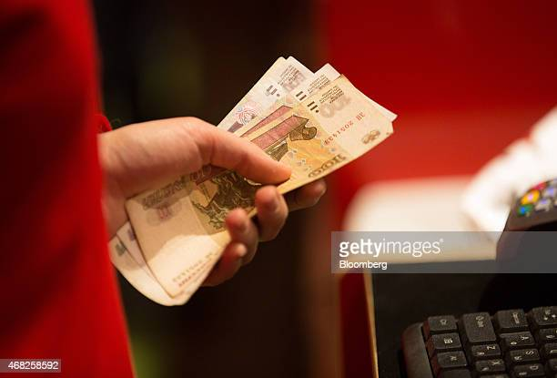 An employee holds ruble banknotes at the payment counter inside the new Hamleys Plc toy store on its opening day in Moscow Russia on Tuesday March 31...