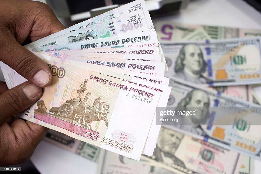 An employee holds Russian Ruble notes over a pile of American Dollar bills in this arranged photograph in London, U.K., on Monday, Aug. 24, 2015. The plunge in the ruble is deepening divides within the free-trade project promoted by Russian President Vladimir Putin to bind former Soviet republics together. Photographer: Jason Alden/Bloomberg via Getty Images