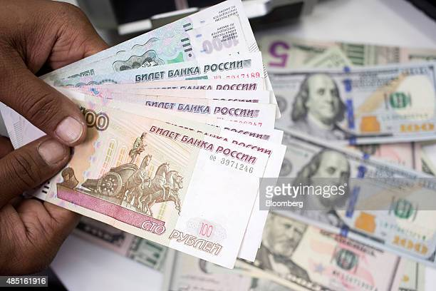 An employee holds Russian Ruble notes over a pile of American Dollar bills in this arranged photograph in London UK on Monday Aug 24 2015 The plunge...