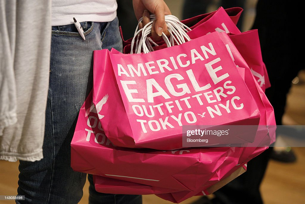 An employee holds shopping bags as she prepares for the opening of an American Eagle Outfitters Inc. store in Tokyo, Japan, on Wednesday, April 18, 2012. American Eagle Outfitters Inc., a retailer of men's and women's casual apparel, opened its first store in Japan inside the Tokyu Plaza Omotesando Harajuku retail complex in the Omotesando district of Tokyo today. Photographer: Kiyoshi Ota/Bloomberg via Getty Images