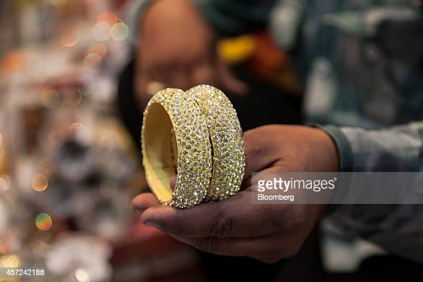 An employee holds two bangles for a photograph at the Lac Bangle store in the Old City area of Jaipur Rajasthan India on Monday Oct 13 2014 Indias...