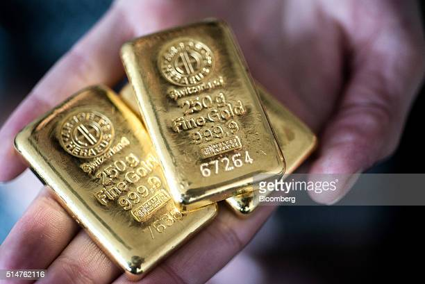 An employee holds two hundred and fifty gram gold bars in this arranged photograph at Solar Capital Gold Zrt in Budapest Hungary on Thursday March 10...