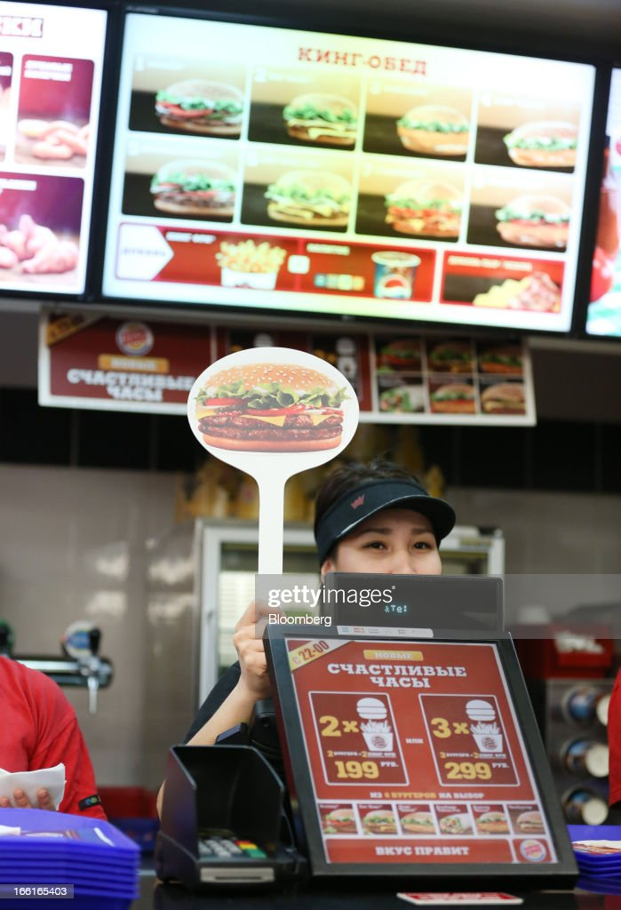 An employee holds up a burger baton behind the cash till on the service counter inside a Burger King fast food restaurant in Moscow, Russia, on Friday, April 5, 2013. McDonald's, which virtually created the market for burgers and fries in the country and convinced Russians it's OK to eat with their hands, must fend off a growing challenge from rivals Burger King Worldwide Inc., Subway Restaurants, Yum! Brands Inc. and Wendy's Co. Photographer: Andrey Rudakov/Bloomberg via Getty Images