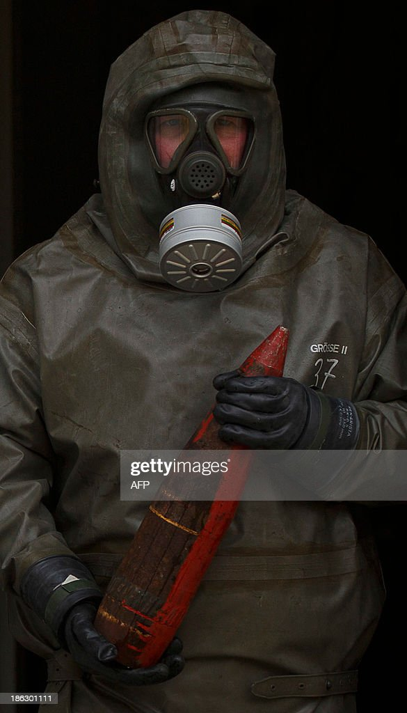 An employee in protective clothing holds a dummy grenade during a demonstration in a chemical weapons disposal facility at GEKA (Gesellschaft zur Entsorgung von chemischen Kampfstoffen und Ruestungsaltlasten) in Munster, northern Germany, on October 30, 2013. The state-owned GEKA is a reference laboratory for the Organsation for the Prohibition of Chemical Weapons (OPCW). AFP PHOTO / PHILIPP GUELLAND