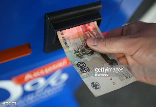 An employee inserts a fifty ruble currency note into an online payment terminal operated by Qiwi Plc at the company's headquarters in Moscow Russia...