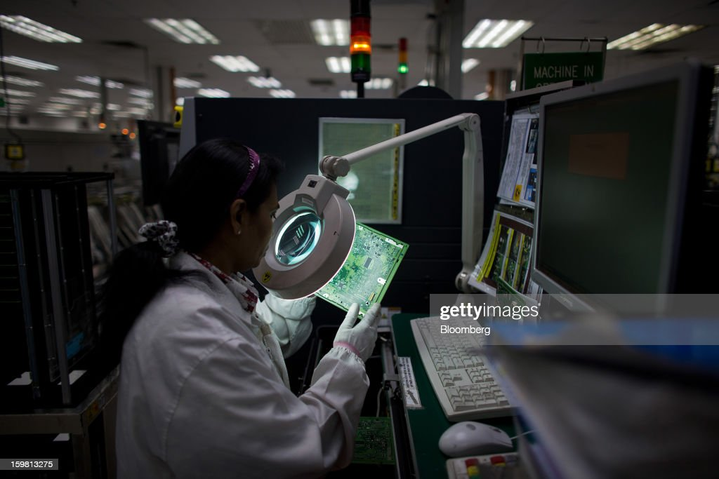 An employee inspects a circuit board for the General Motors NextGen Navigation Processing Unit, produced by Robert Bosch GmbH for General Motors Co. (GM), on the production line at the Robert Bosch plant in the Bayan Lepas Industrial Zone on Penang Island, Malaysia, on Thursday, Jan. 17, 2013. Robert Bosch GmbH is the world's largest automotive supplier. Photographer: Lam Yik Fei/Bloomberg via Getty Images