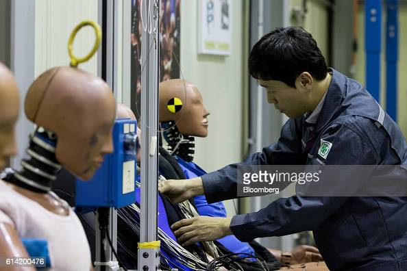 An employee inspects a crash test dummy at the Korea Automobile Insurance Repair Research and Training Center operated by the Korea Insurance...