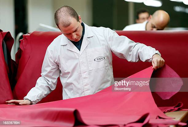 An employee inspects a dyed leather hide for imperfections during the manufacture of Tod's SpA luxury shoes inside the workshop at the company's...
