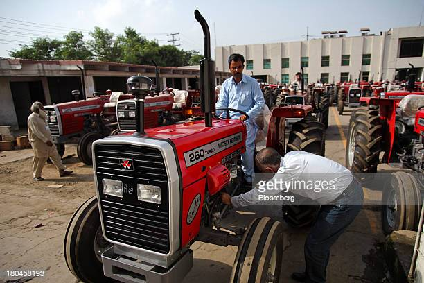 An employee inspects a finished Massey Fergusonbranded tractor outside the Millat Tractors Ltd assembly plant in Lahore Pakistan on Thursday Aug 29...