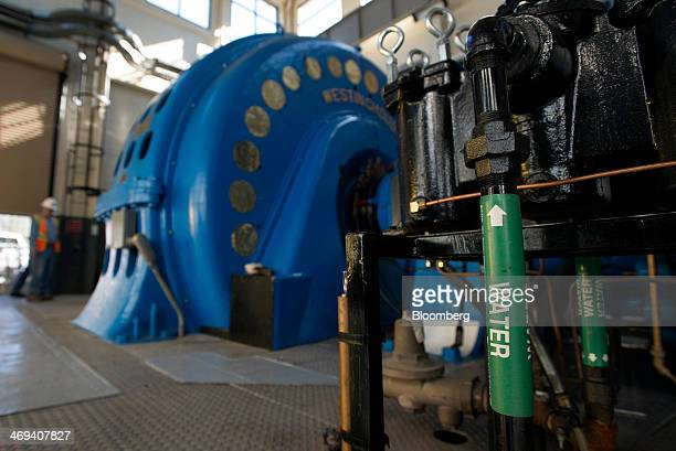 An employee inspects a hydroelectric turbine at the Pacific Gas Electric Co Wise Powerhouse hydroelectric power plant in Auburn California US on...