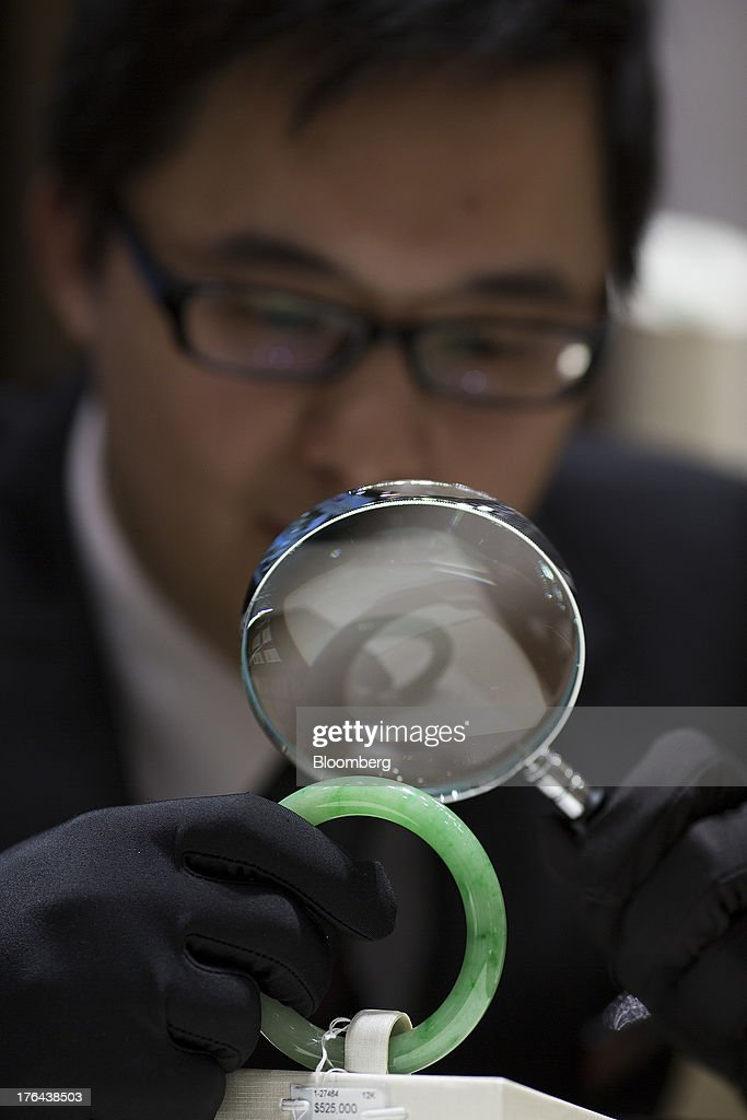 An employee inspects a jade bangle with a magnifying glass in an arranged photograph at a Chow Tai Fook Jewellery Group Ltd. retail store in the Central district of Hong Kong, China, on Tuesday, July 23, 2013. The value of the precious gem is surging with Chinas wealthy snapping up jade necklaces, rings and bracelets as long-term investments. Photographer: Jerome Favre/Bloomberg via Getty Images