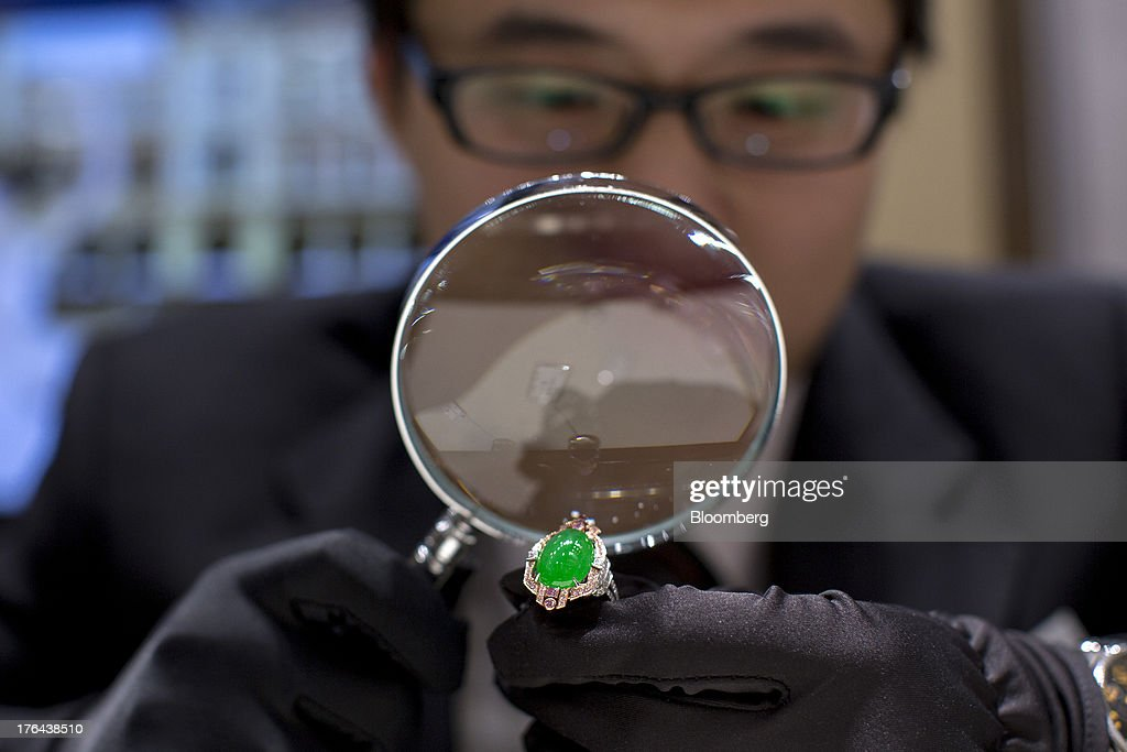 An employee inspects a jade ring with a magnifying glass in an arranged photograph at a Chow Tai Fook Jewellery Group Ltd. retail store in the Central district of Hong Kong, China, on Tuesday, July 23, 2013. The value of the precious gem is surging with Chinas wealthy snapping up jade necklaces, rings and bracelets as long-term investments. Photographer: Jerome Favre/Bloomberg via Getty Images