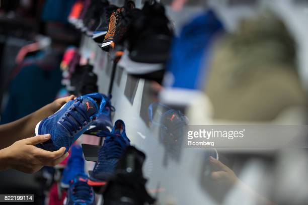An employee inspects a men's running shoe inside a Puma SE sportswear clothing store in Berlin Germany on Tuesday July 25 2017 Puma increased its...