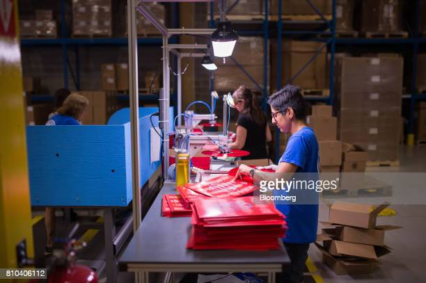 An employee inspects a newly pressed vinyl record before packaging at the Precision Record Pressing facility in Burlington Ontario Canada on Friday...