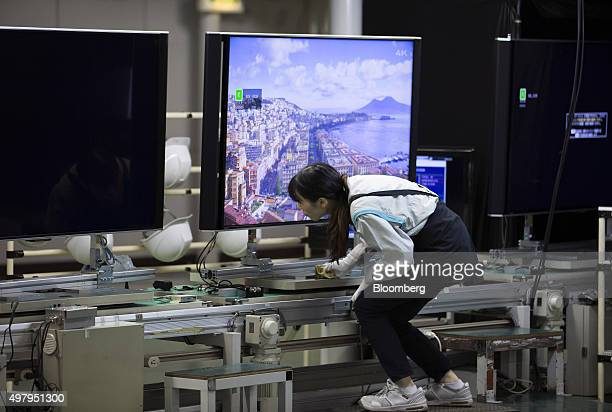 An employee inspects a Sharp Corp Aquos liquid crystal display television on the production line of the company's plant in Yaita Tochigi Prefecture...