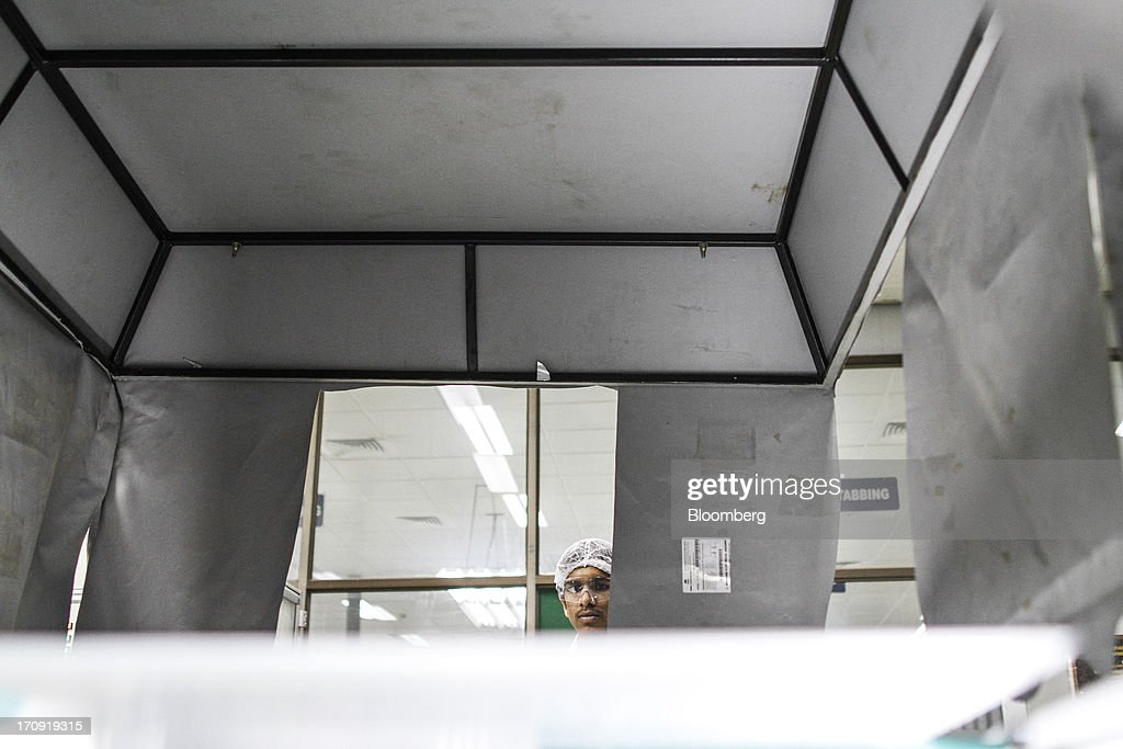 An employee inspects a solar panel inside an inspection chamber on the solar photovoltaic module production line at the Tata Power Solar Systems Ltd. manufacturing plant in Bangalore, India, on Tuesday, June 11, 2013. Tata Groups solar unit is expanding its business building plants for customers, forecasting that offices and factories will be paying more for grid power than solar by 2016 in most Indian states. Photographer: Dhiraj Singh/Bloomberg via Getty Images