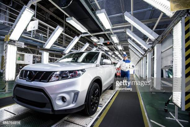 An employee inspects a Suzuki Vitara compact sportsutility vehicle on the assembly line inside the Suzuki Motor Corp plant in Esztergom Hungary on...