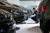 An employee inspects a Volkswagen automobile in the used car sales area of the Volkswagen AG showroom in Berlin Germany on Thursday Aug 6 2015 In...