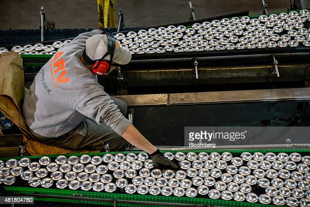 An employee inspects beer cans moving along the production line at the Ambev SA bottling facility in Lages Brazil on Friday July 17 2015 Ambev SA is...