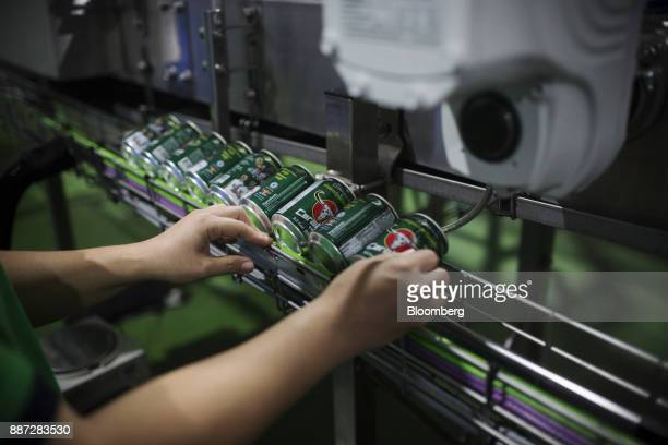An employee inspects cans of Carabao energy drink on the production line at the Carabao Group Pcl plant in Chachoengsao Chachoengsao Province...