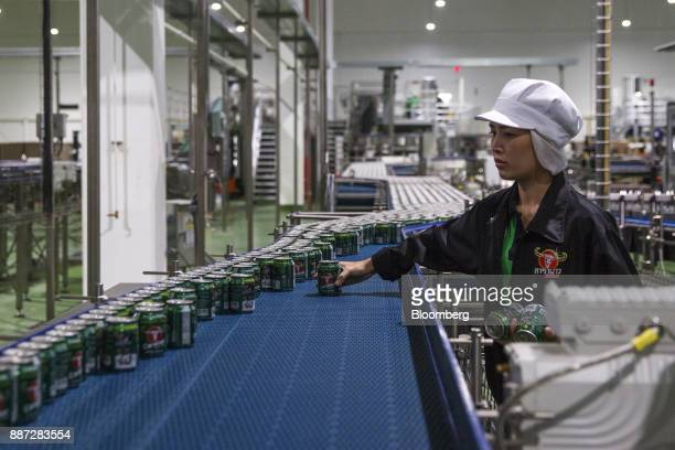 An employee inspects Carabao energy drink cans on the production line at the Carabao Group Pcl plant in Chachoengsao Chachoengsao Province Thailand...