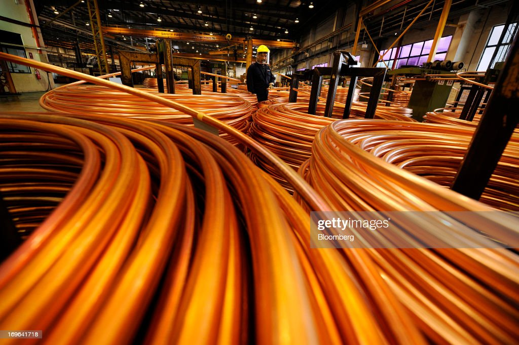 An employee inspects coils of copper rod at the Luvata Malaysia Bhd. plant in Pasir Gudang, Johor, Malaysia, on Monday, May 13, 2013. At a time when copper stockpiles are rising to the highest in a decade, manufacturers are paying the biggest premiums for the metal in as much as seven years as financing deals lock up supply and extend lines at warehouses. Photographer: Munshi Ahmed/Bloomberg via Getty Images