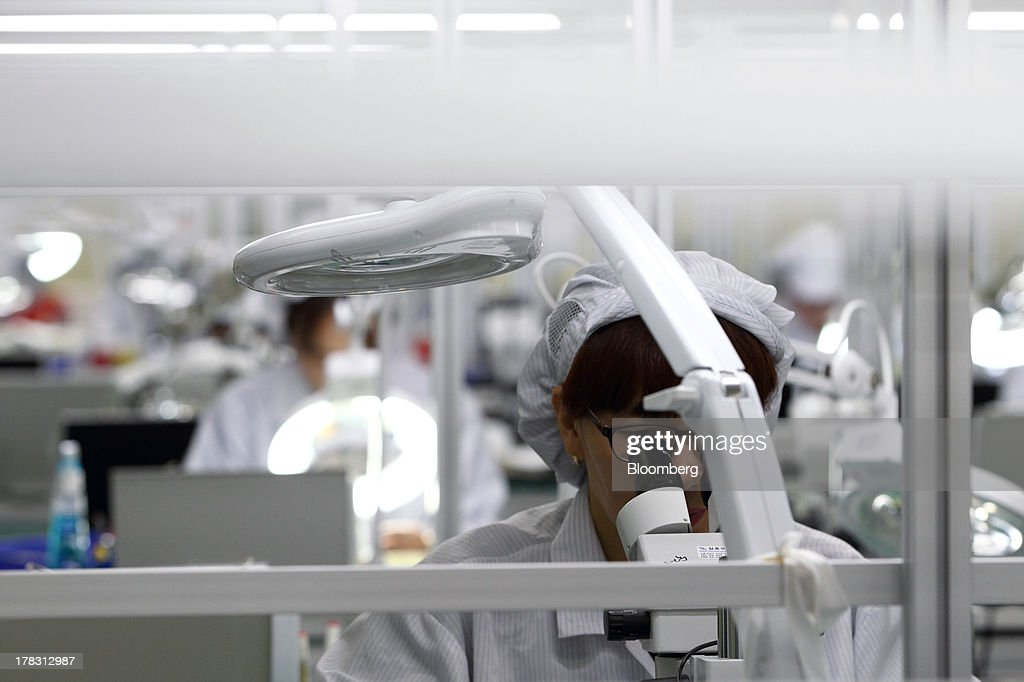 An employee inspects Flexible Printed Circuit Boards (F-PCB) through a microscope on the production line at the Seil Electronics Co. factory in Incheon, South Korea, on Wednesday, Aug. 28, 2013. South Korea has surpassed Brazil, Russia and India to become the second-biggest emerging stock market for the first time since 2006, as a stable won and record current-account surplus lure investors. Photographer: SeongJoon Cho/Bloomberg via Getty Images