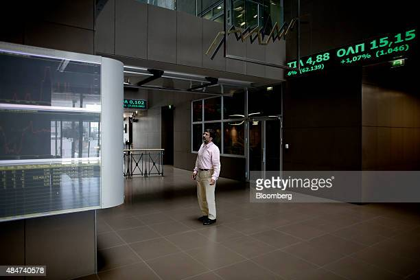 An employee inspects Greek stock prices on a ticker screen at the Athens Stock Exchange SA in Athens Greece on Friday Aug 21 2015 The return on Greek...