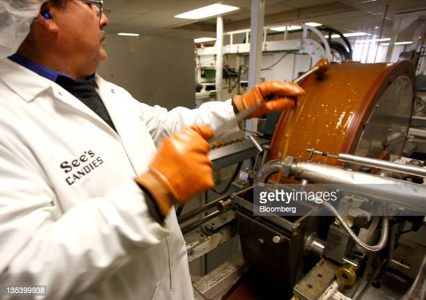 An employee inspects hot liquid butterscotch on a cooling roller at the See's Candies Inc lollipop factory in Burlingame California US on Thursday...