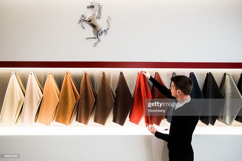 An employee inspects interior leather samples for Ferrari sports cars in the showroom of an automobile dealership in Budapest, Hungary, on Wednesday, May 15, 2013. Ferrari SpA, the Italian supercar manufacturer owned by Fiat SpA, plans to reduce sales to fewer than 7,000 vehicles this year to 'maintain the exclusivity' of the brand. Photographer: Akos Stiller/Bloomberg via Getty Images
