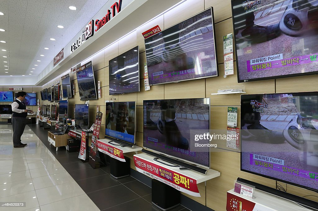An employee inspects LG Electronics Inc. Cinema 3D televisions, which use LG Display Co. panels, at the company's Bestshop store in Seoul, South Korea, on Wednesday, Jan. 22, 2014. LG Electronics, the worlds second-largest seller of televisions, is scheduled to announce fourth-quarter earnings on Jan. 27. Photographer: SeongJoon Cho/Bloomberg via Getty Images