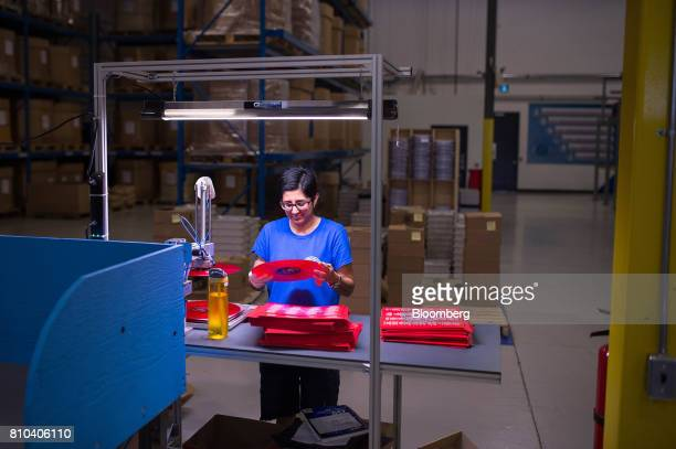 An employee inspects of a newly pressed vinyl record before packaging at the Precision Record Pressing facility in Burlington Ontario Canada on...
