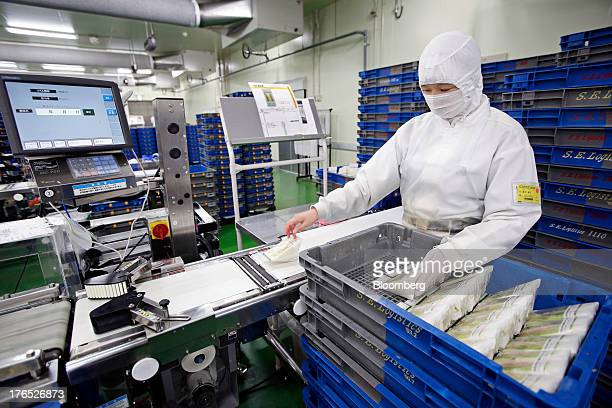 An employee inspects packaged hamandcheese sandwiches for Seven I Holdings Co's 7Eleven convenience stores on the production line of Prime Delica...