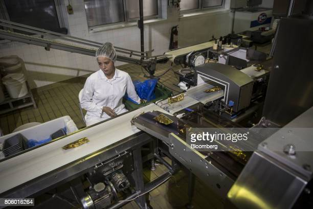 An employee inspects packaged King ice creams on a conveyor belt on the production line at the Ledo dd ice cream plant operated by Agrokor dd in...