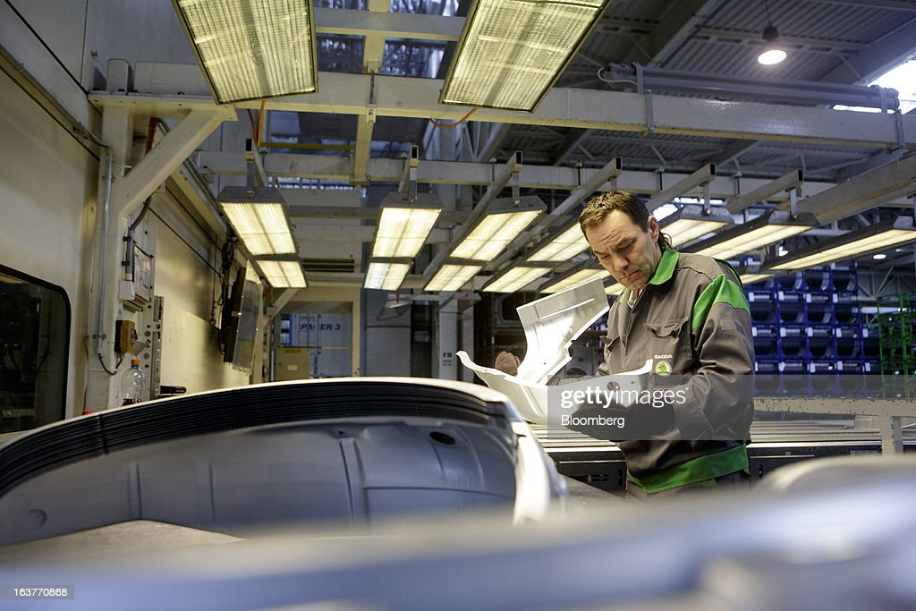 An employee inspects parts before assembly on the automobile production line at Skoda Autos AS in Mlada Boleslav, Czech Republic, on Friday, March 15, 2013. VW, which also owns the Porsche luxury-auto brand as well as the Skoda and Seat volume marques, will build at least 10 plants globally, including seven in China, Martin Winterkorn, chief executive officer of Volkswagen AG, said. Photographer: Martin Divisek/Bloomberg via Getty Images