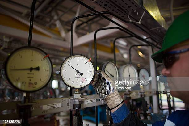 An employee inspects pressure gauges at an oil plant operated by Salym Petroleum in Salym KhantyMansi autonomous region Russia on Wednesday July 3...