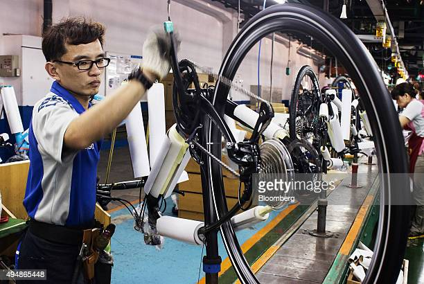 An employee inspects the wheel of a bicycle on the assembly line of the Giant Manufacturing Co bicycle manufacturing facility in Taichung Taiwan on...