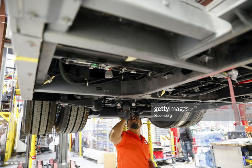An employee inspects underneath an electric bus at the BYD Coach and Bus factory in Lancaster, California, U.S., on Thursday, Oct. 5, 2017. BYD unveiled the newly expanded 450,000 square foot factory on Friday, North America's largest electric bus manufacturing facility. Photographer: Patrick T. Fallon/Bloomberg via Getty Images