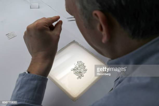 An employee inspects unpolished diamonds at the De Beers SA headquarters on Charterhouse Street in London UK on Wednesday Feb 1 2017 Number 17...