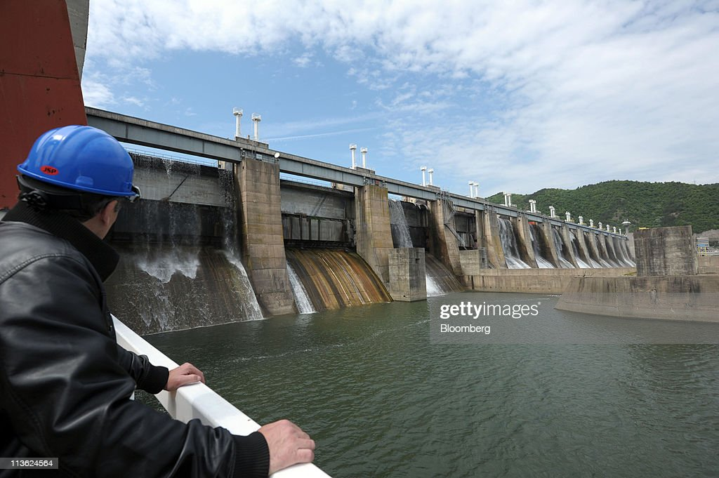 An employee inspects water exiting the spillways at Djerdap 1, Serbia's largest hydro-electric power plant which is operated by Elektroprivreda Srbije, on the Danube river in Kladovo, Serbia, on Wednesday, May 4, 2011. Serbia expects as much as 9 billion euros ($13.4 billion) to be invested in the overhaul and development of its energy sector by 2015, according to Dusan Mrakic, a state secretary with the Energy and Mining Ministry. Photographer: Oliver Bunic/Bloomberg via Getty Images