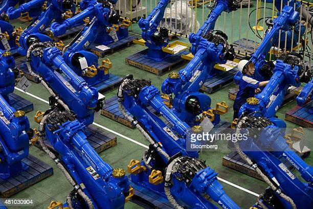 An employee inspects Yaskawa Electric Corp Motoman robots bound for shipment at the company's factory in Kitakyushu Japan on Thursday July 16 2015 In...