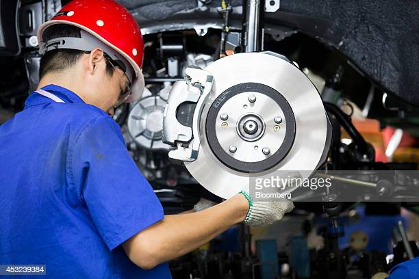 An employee installs brake pads on a BYD Co S6 sportutility vehicle at the company's assembly plant in the Pingshan district of Shenzhen China on...