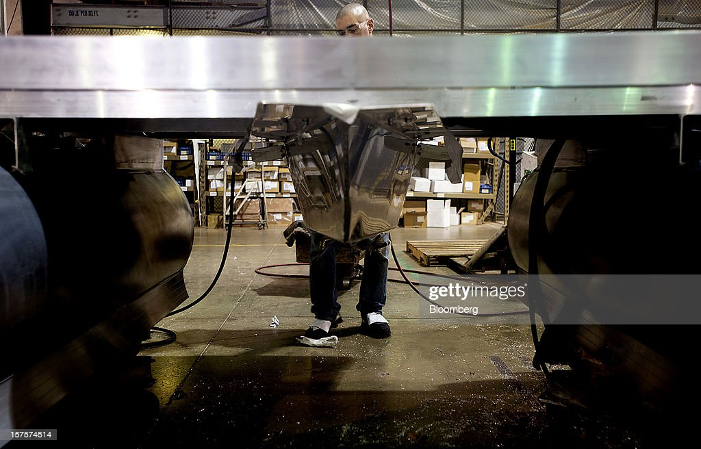An employee installs flooring on the main deck of a pontoon boat on the assembly line at the Nautic Global Group production facility in Elkhart, Indiana, U.S., on Tuesday, Dec 4, 2012. The U.S. Census Bureau is scheduled to release factory orders data on Dec. 5. Photographer: Ty Wright/Bloomberg via Getty Images