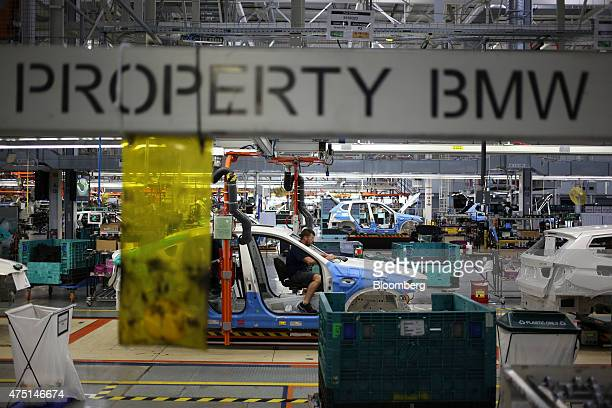 An employee installs interior accessories inside a Bayerische Motoren Werke AG X4 sports utility vehicle on the assembly line at the BMW...