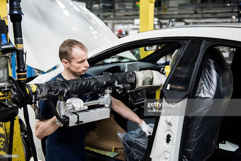 An employee installs the seats in an automobile on the production line at the Mercedes-Benz AG automobile plant, operated by Daimler AG, in Kecskemet, Hungary, on Friday, April 29, 2016. Daimler's Mercedes factory will produce a new generation of compact vehicles, totaling Daimler's investment in Hungary to more than $1.8 billion. Photographer: Akos Stiller/Bloomberg via Getty Images