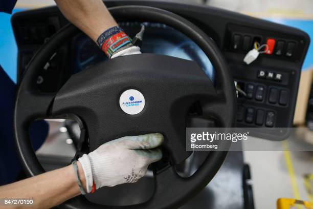 An employee installs the steering wheel to an Enviro 200 bus at the Alexander Dennis Ltd factory in Guildford UK on Monday Sept 11 2017 Manufacturing...