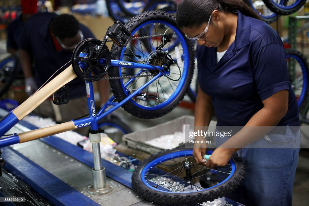 An employee installs wheels on a Boys MT20 model bicycle frame at The Kent International Inc. Bicycle Corporation of America brand Assembly facility in Manning, South Carolina, U.S., on Sunday, June 25, 2017. Almost all of the roughly 18 million bicycles sold each year in the U.S. come from China and Taiwan. This year, about 130 workers at the Bicycle Corporation of America's new factory will assemble 350,000 bikes in the U.S. Photographer: Travis Dove/Bloomberg via Getty Images
